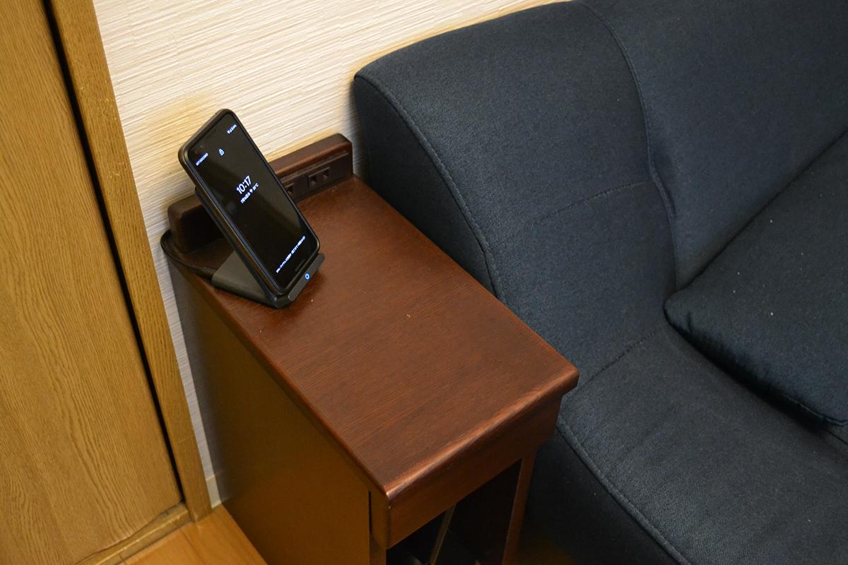 サイドテーブルの上に置かれたスマホのワイヤレス充電器