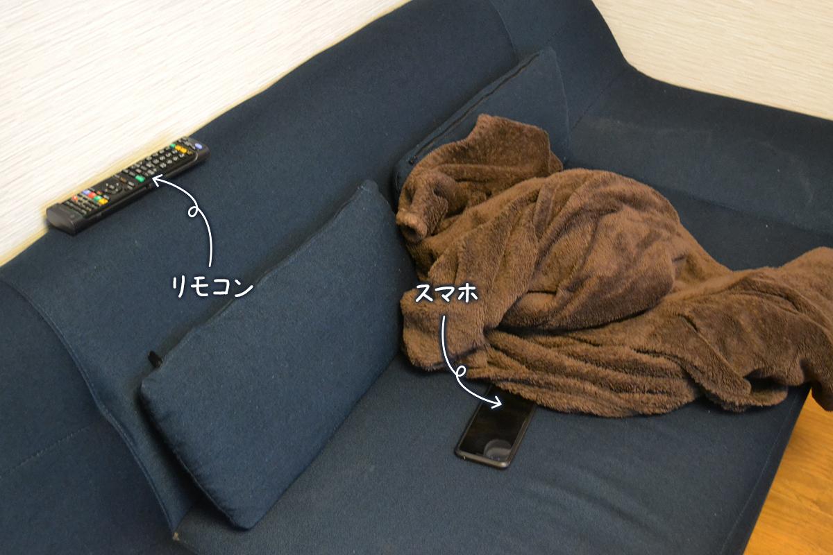 ソファーの上に転がるスマホとリモコン