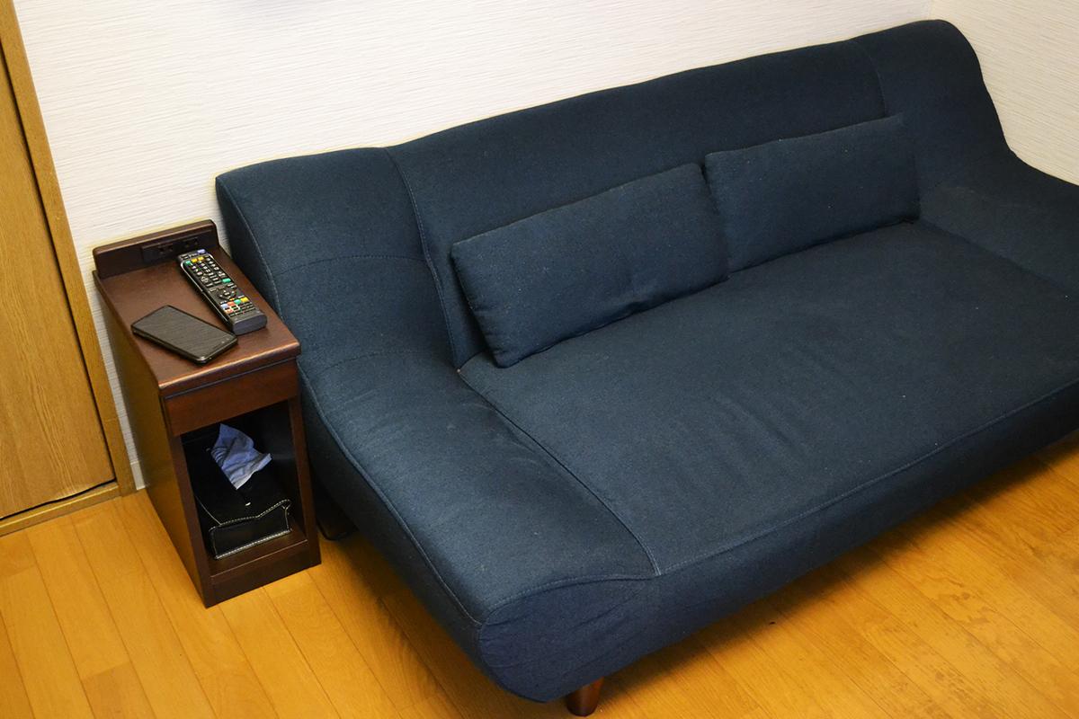 ダークブラウンのナイトテーブルとネイビー色のソファー